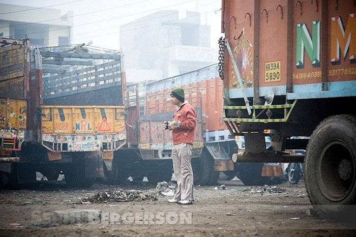 A truck driver having his first morning chai on a foggy winter day in Punjab