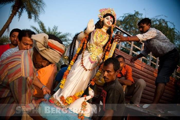 Worshipers unload an idol of the Hindu goddess Saraswati from a truck during celebration of Durga Puja festival, some forty km from Delhi