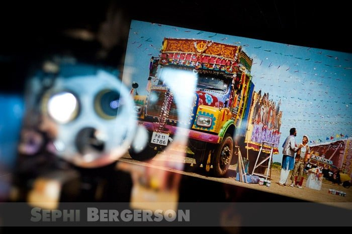 A decorated truck is featured in the Bollywood movie 'Dil Bole Hadippa' (2009, Yash Raj films) seen from the projection room of a cinema hall in Noida (UP). The movie projector is reflected in the glass window of the projection room.