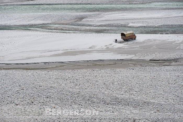 People load a truck with sand from a river bed on the way to Gangotri in the high Himalaya mountains